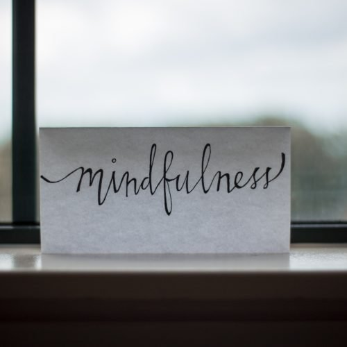 A piece of paper sits on a windowsill. The word mindfulness is written across it.