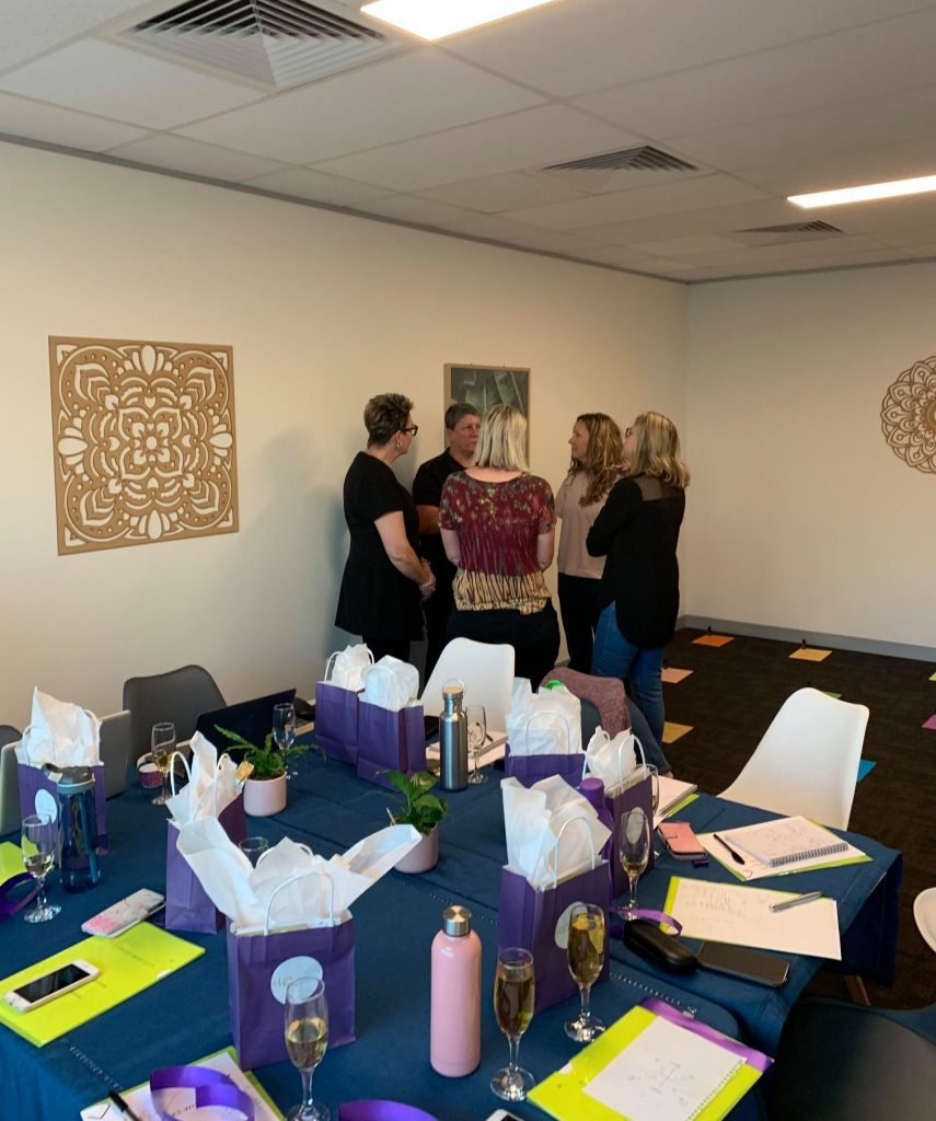 The Ohana Studio set up for a team building workshop. A group of ladies stand chatting behind a clothed large table with gift bags, snack and drinks plus notepads and pens.
