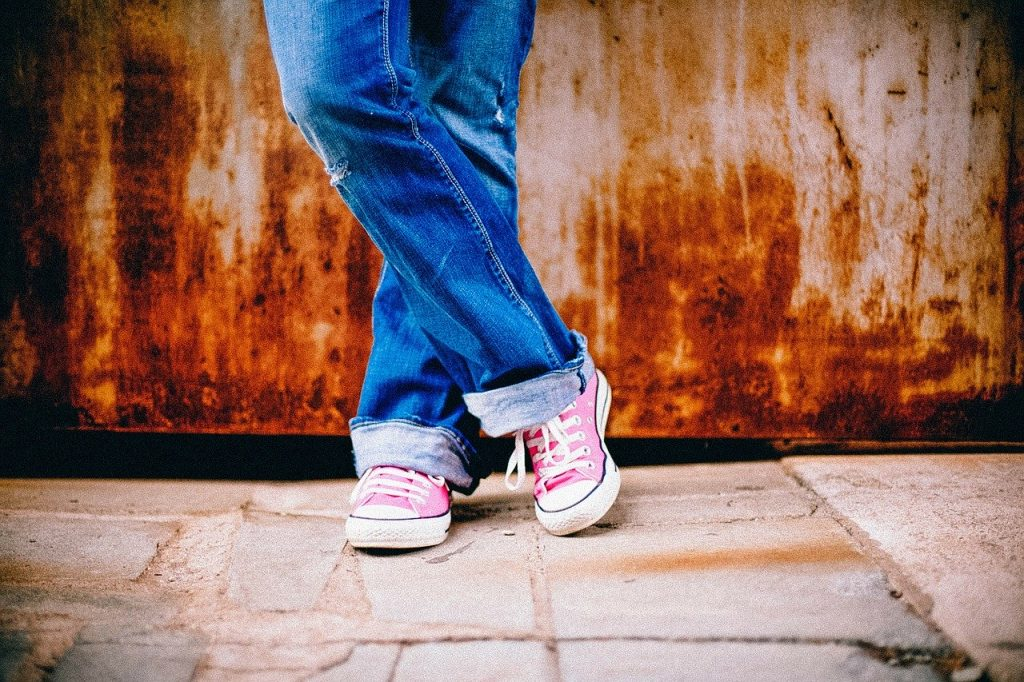 Image shows legs of a teen child wearing jeans and pink sneakers. Legs are crossed at the ankles. PMS in teens is often at its lifetime peak.