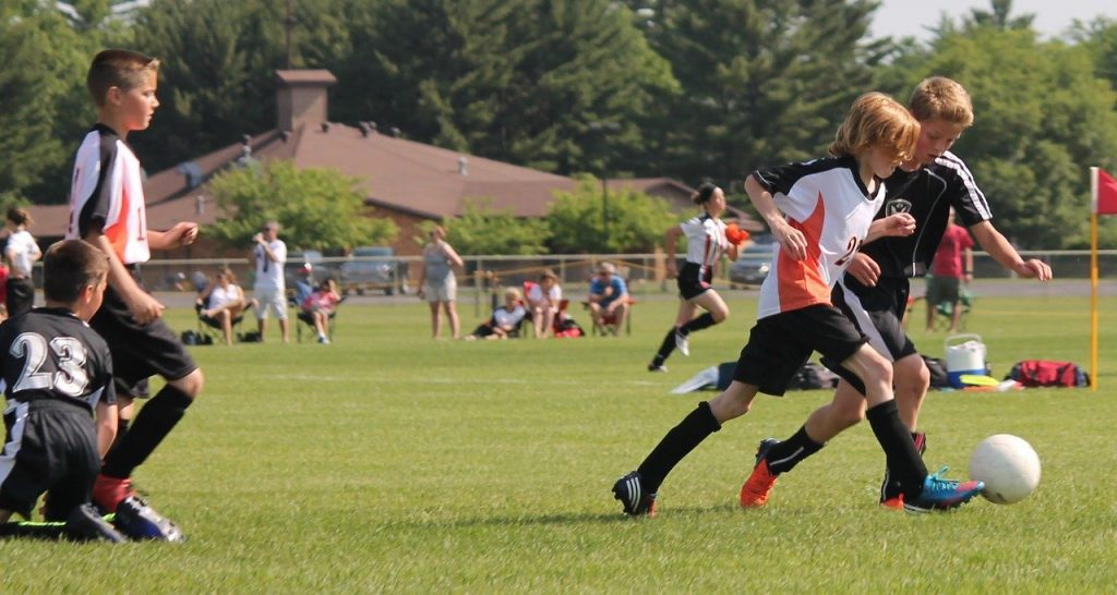 Two boys playing soccer on a field. For highly active kids, or those that may not enjoy a diet with a broad range of foods, supplementation can be useful to supercharge their healing.
