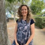 A woman stands beside a tree smiling. Mikaela Duffy, naturopathic and nutritional services at Ohana Health and Wellbeing