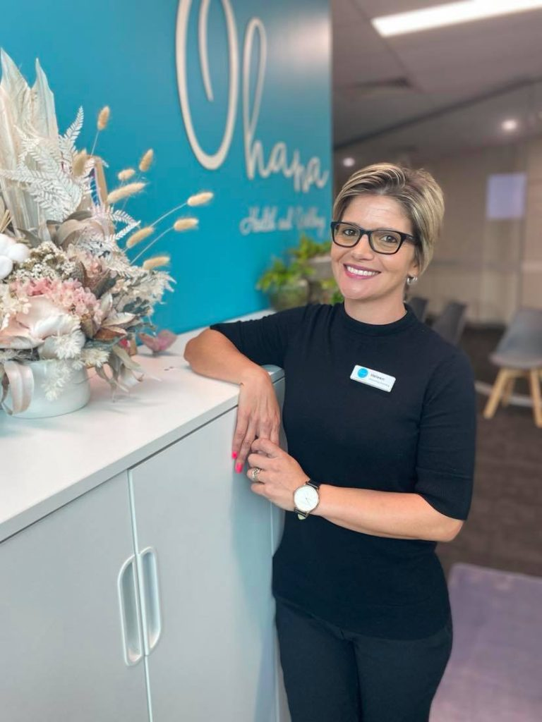 Photo is of a woman with short brown hair leaning on a cupboard wearing glasses and smiling. Heleen from Ohana Chiropractic